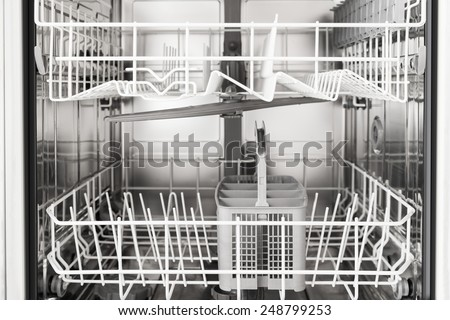 Close-up Photo Of An Empty Opened Dishwasher - stock photo