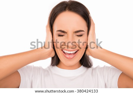 Close up photo of angry young woman plugging ears with hands and screaming - stock photo