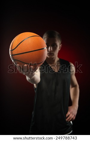 Close-up photo of ball in serious young Caucasian basketball athlete hand - stock photo