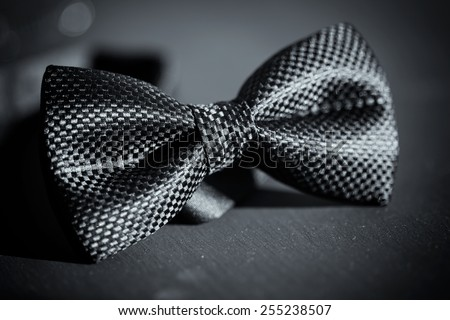 Close-up photo of black bow tie on dark background - stock photo