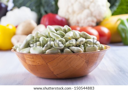 Close up photo of edible vegetables - a broad bean with some vegetables in the background on a solid  bright blue wooden table - stock photo