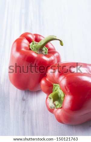 Close up photo of edible vegetables - a red bell pepper on a solid light blue wooden table - stock photo