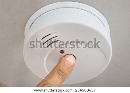 Close-up Photo Of Finger Testing Smoke Detector - stock photo