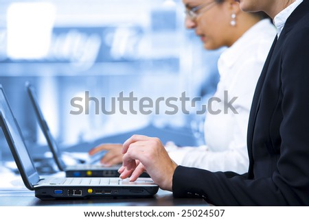 Close up photo of  fingers on keyboard in business environment - stock photo