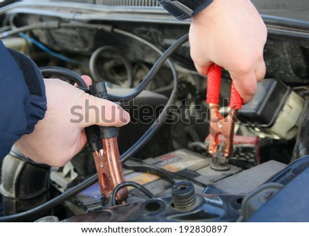 Close up photo of how mechanic charges the battery car - stock photo