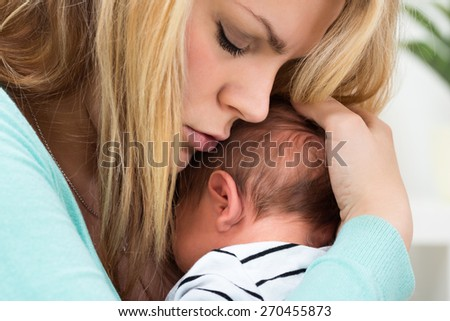 Close-up Photo Of Mother Carrying Newborn Baby - stock photo