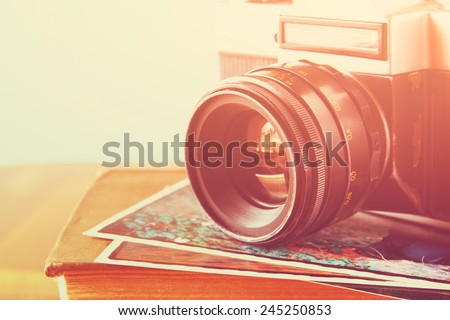 close up photo of old camera lens over wooden table. image is retro filtered. selective focus - stock photo