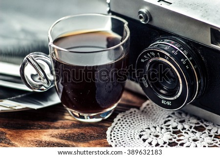 Close up photo of old, vintage camera lens with cap of coffee and black and white photos over wooden table. Nostalgic holidays background. Memories concept. Image is retro filtered. Selective focus - stock photo