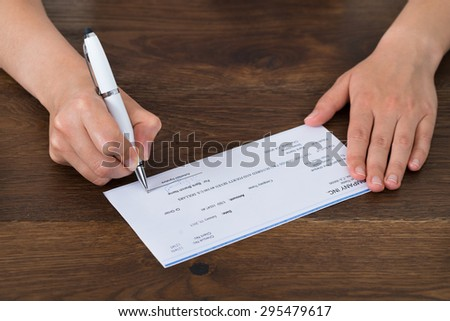Close-up Photo Of Person Hands Signing Cheque - stock photo
