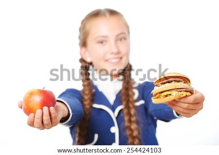 Close up photo of smiling school girl with apple and hamburger. Isolated on white background. Concept for healthy eating at school - stock photo