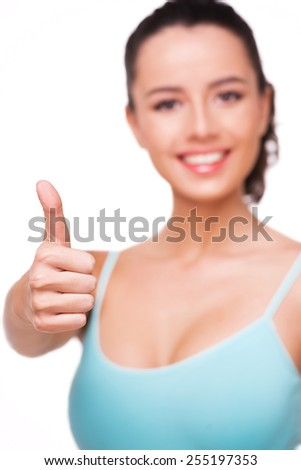 Close up photo of sporty young woman showing thumb up, isolated on white background - stock photo