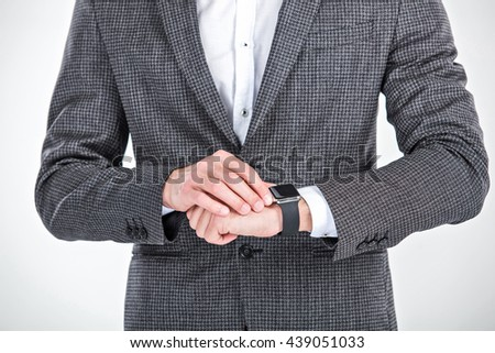 Close up photo of stylish handsome young man isolated on white background. Man using smart watch - stock photo