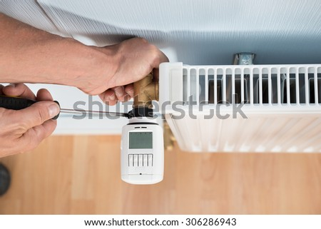 Close-up Photo Of Technician Installing Digital Thermostat Using Screwdriver - stock photo