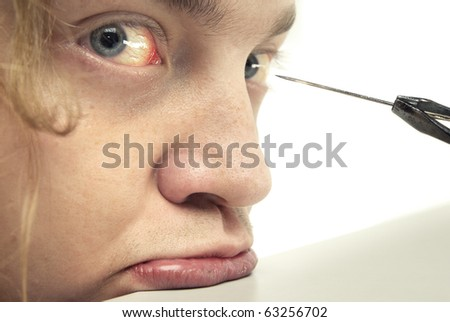 Close-up photo of the afraid man and metal niddle near his eyes - stock photo