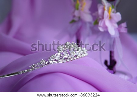 Close-up photo of the silver or platinum (white gold) diadem with diamonds on a lilac background. In the background are visible flower decorations - stock photo