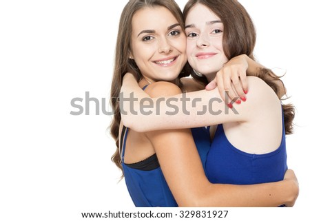 Close up photo of two young sisters embracing each other looking very happy and smiling, isolated on white background - stock photo