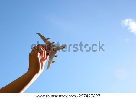 close up photo of woman's hand holding toy airplane against blue sky   - stock photo