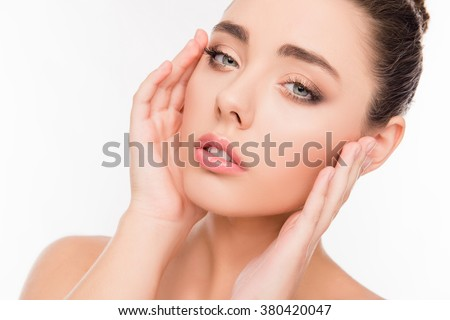 Close up photo of  young cute girl with seductive look touching face - stock photo