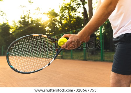 Close up photo of young man on tennis court. Man playing tennis. Man is ready to throw tennis ball. Beautiful forest area as background - stock photo