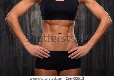 Close up photo of young mixed race sporty woman. She demonstrating her biceps and slim belly. Fitness concept - stock photo
