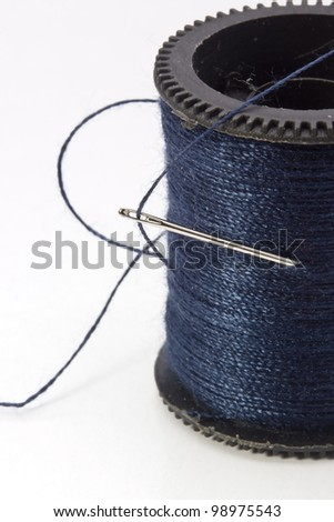 Close-up photograph of a blue thread spool and needle. - stock photo