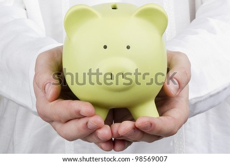Close-up photograph of a green piggy bank in man's hands. - stock photo