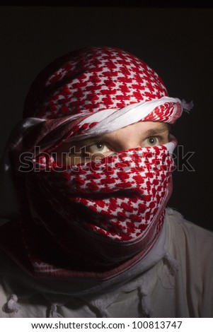 Close-up photograph of a man in a red keffiyeh. - stock photo