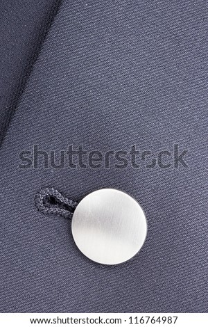 Close-up photograph of a silver button on gray material. - stock photo