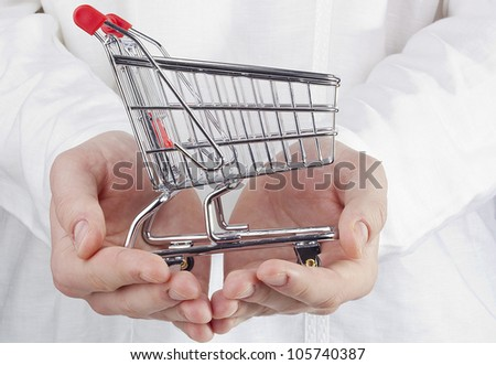 Close-up photograph of man's hands holding a shopping cart. - stock photo
