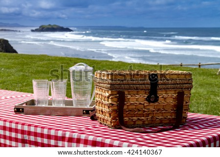 Close up picnic along the coast overlooking the Pacific Ocean with picnic basket and red checkered tablecloth on wooden picnic table - stock photo