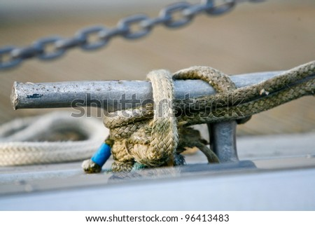 close up picture of a cleat and rope on a boat, a motorboat moored at ham in middlesex UK - stock photo