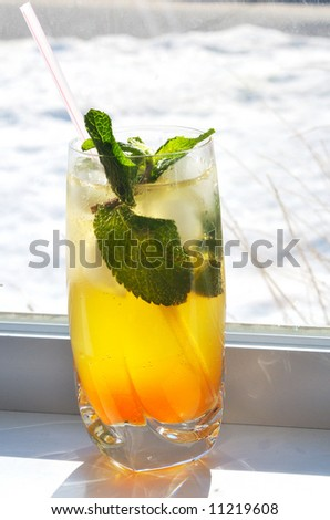 Close-up picture of a glass of Mojito cocktail with winter snow-covered street on the background - stock photo