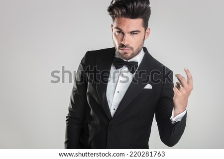 Close up picture of a handsome young man in tuxedo snapping his finger while looking at the camera - stock photo