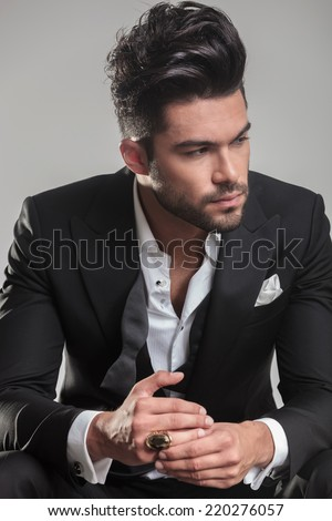 Close up picture of a serious young man in tuxedo, looking away from the camera, thinking. - stock photo
