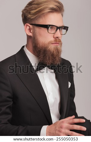 Close up picture of a young business man holding his hand on the knee while sitting, looking away from the camera. - stock photo
