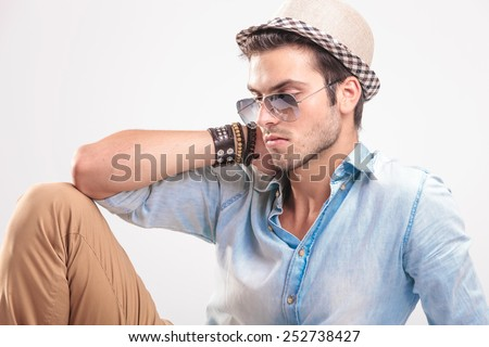 Close up picture of a young casual man looking down while holding his hand to his neck. - stock photo