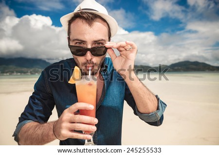 Close up picture of a young casual man on the beach drinking a orange cocktail with a straw while taking off his sunglasses. - stock photo