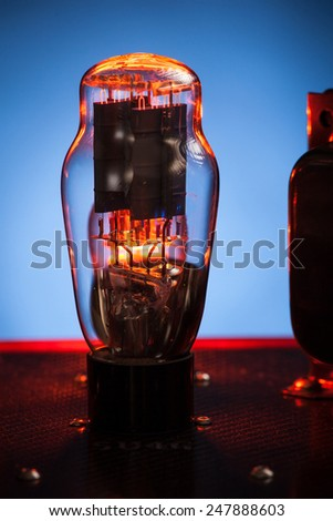 Close up picture of electronic vacuum tube, with incandescendent filament and blue background - stock photo