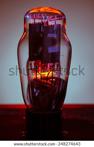 Close up picture of electronic vacuum tube,with incandescent filament and grey background - stock photo