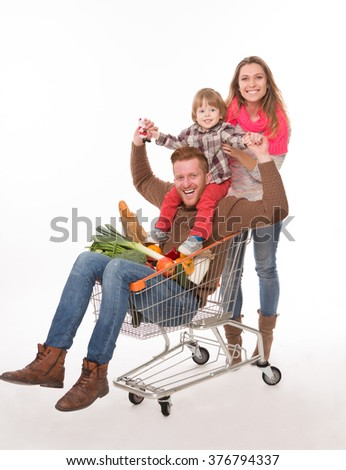 Close-up picture of happy family with a shopping cart in supermarket. Parents and their baby buying products. - stock photo