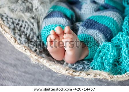 Close up picture of new born baby feet in knitted plaid - stock photo