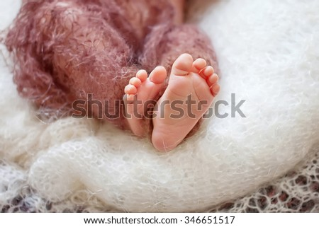 Close up picture of new born baby feet on a brown plaid - stock photo