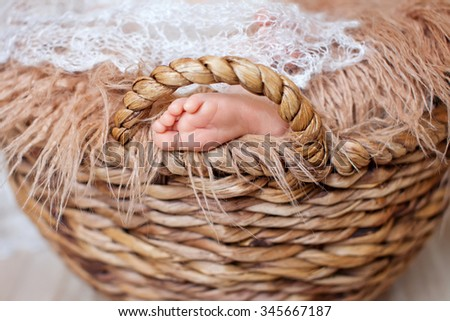Close up picture of new born baby feet on a white plaid in the wicker basket - stock photo