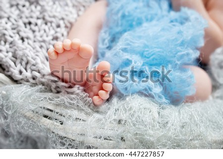 Close up picture of new born baby feet on knitted plaid in a wattled basket - stock photo