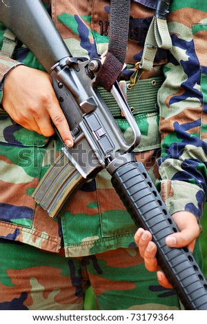 Close-up picture of soldier carrying  M 16  in combat training. - stock photo
