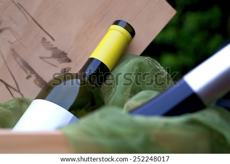 close-up picture of wine-bottles in a wooden winebox with green cloth - stock photo