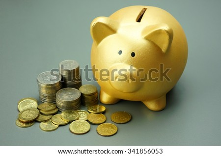 Close up piggy bank and pile of coins - stock photo