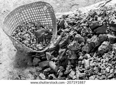 Close up pile of charcoal with bamboo basket in black and white tone - stock photo