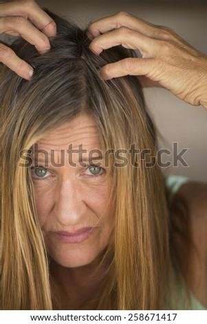 Close up Portrait attractive mature woman tearing her long brunette hair with hands, unhappy, stressed, blurred background. - stock photo