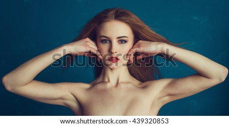 Close-up portrait beautiful girl on a blue background. Woman showing her armpits. Spa, skincare and cosmetology female shoot. - stock photo